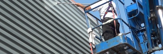Spray painting the first coat of PVC94 cladding paint
